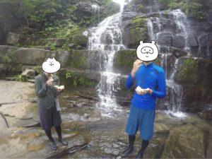 滝のそばでパイナップルを食べる