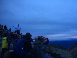 岩の上に立ち、山並みを解説したりする神主さん